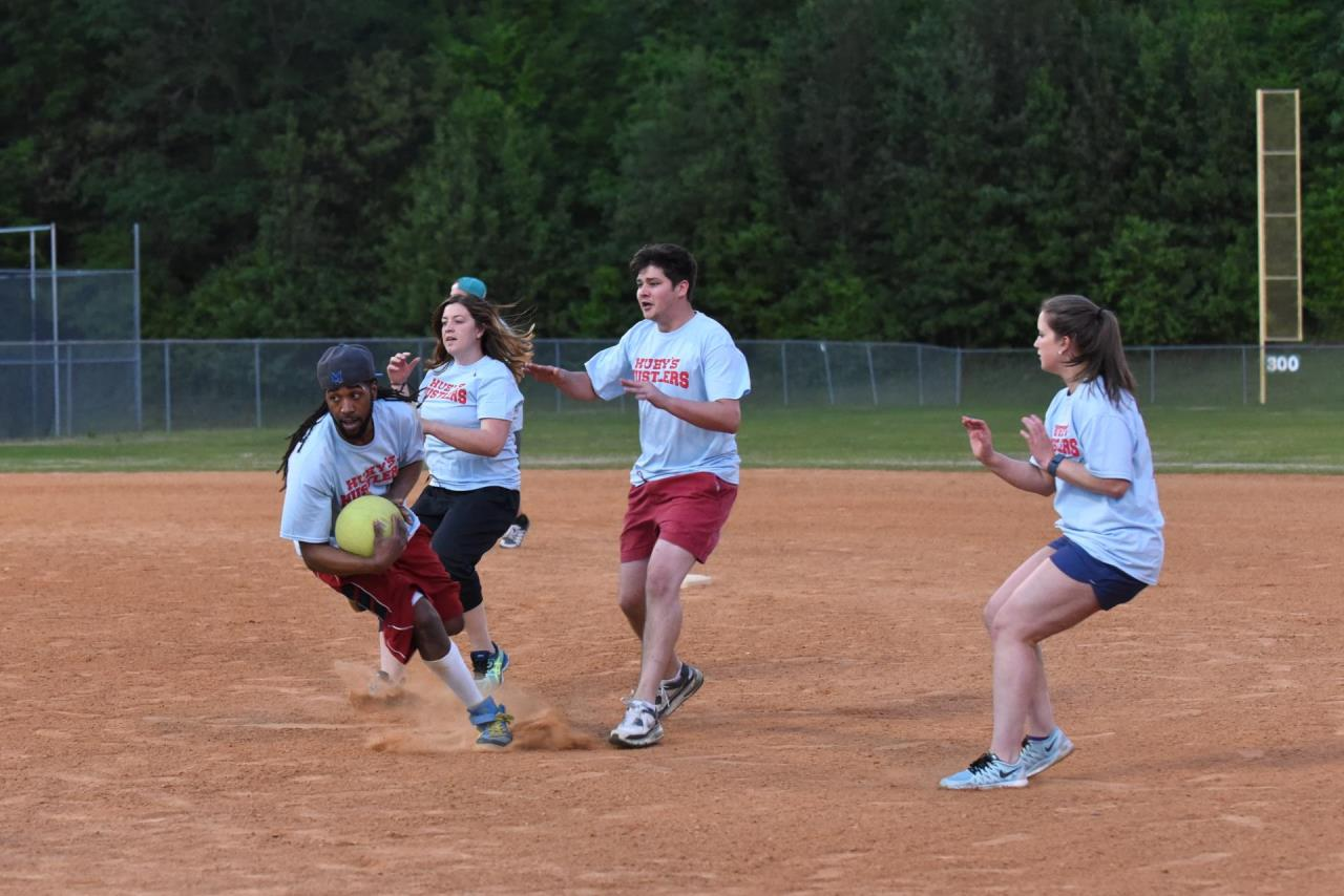 adults running playing kickball