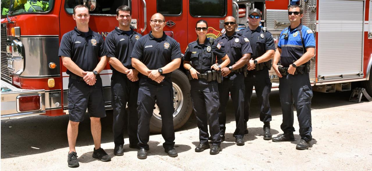 Firefighters and police officers standing in front of a fire truck