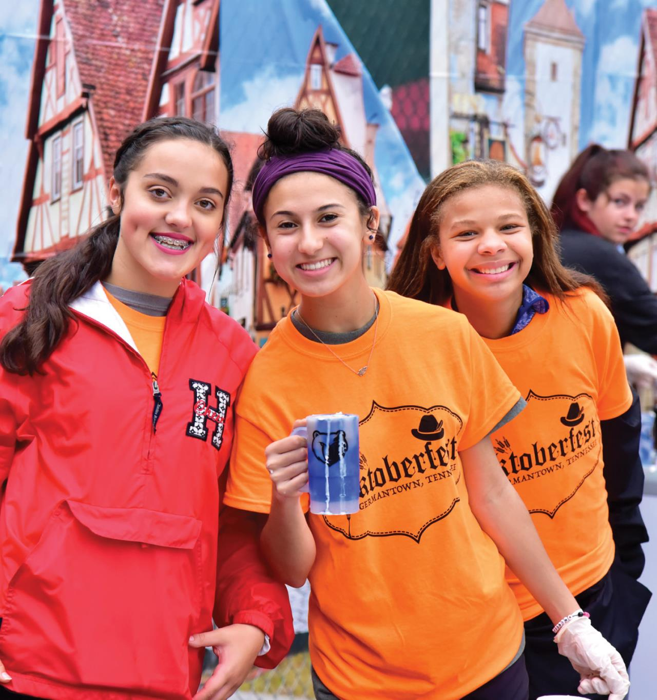 tghree smiling girls volunteer at Oktoberfest